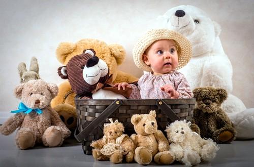 малыш в корзине и плюшевые игрушки